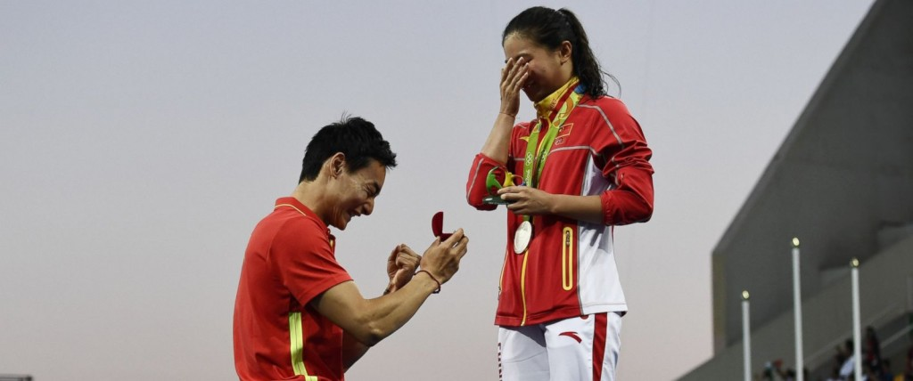 Silver medallist China's He Zi proposed to by Chinese diver Qin Kai after the podium ceremony of the Women's diving 3m Springboard Final at the Rio 2016 Olympic Games